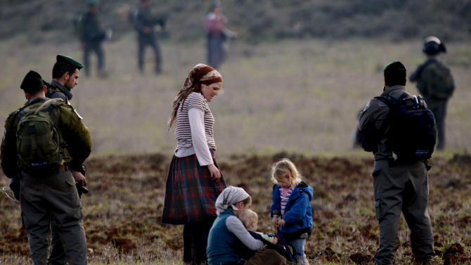 Surrounded by Israeli border police, Jewish settlers from the Esh Kodesh settlement outpost, sit in a field in an attempt to prevent Palestinians from farming land in the northern West Bank, Wednesday, Jan. 2, 2013. Both the settlers and Palestinians living in the area claim ownership of the disputed land. (AP Photo/Majdi Mohammed)