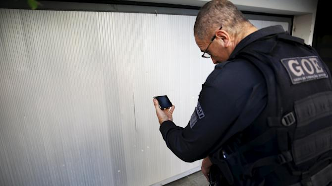 Police officer watches a CCTV footage of a bomb attack on a mobile phone, at the entrance of the Lula Institute in Sao Paulo