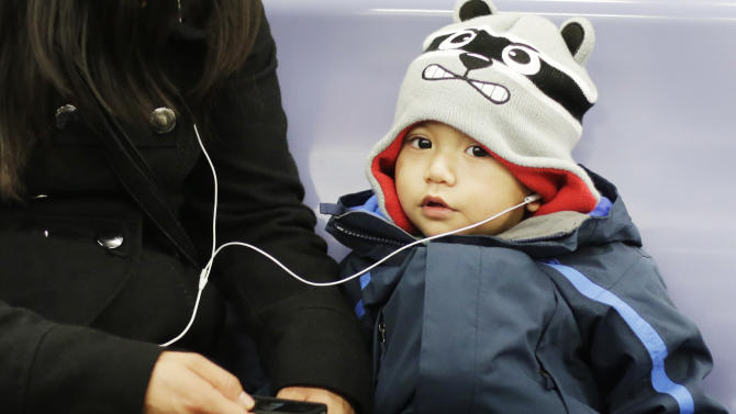 In this photo of Tuesday, March 5, 2013, a young boy listens to music by sharing an earphone with his mother while riding a New York subway. Add cranked-up earphones to the list of health dangers Mayor Michael Bloomberg wants New Yorkers to quit. City health officials plan to warn young people with a public service campaign that they risk hearing loss from listening to music at high volume on personal music players. (AP Photo/Mark Lennihan)