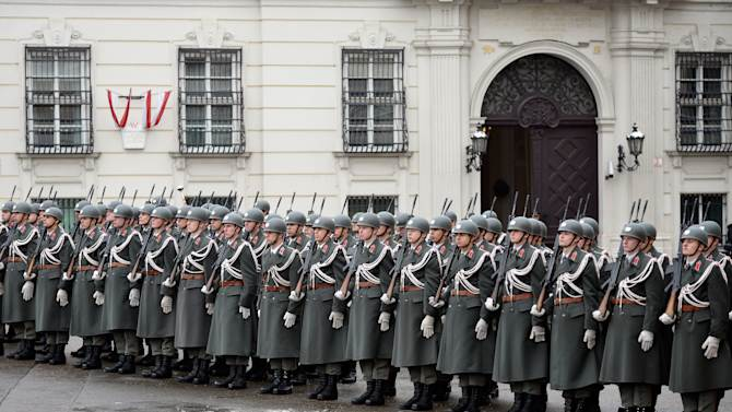 FILE - In this Jan. 15, 2013 file photo Austrian army soldiers stand in front of the chancellery in Vienna, Austria. Austrians eligible to vote are called to participate an army referendum, Sunday, Jan. 20, 2013. At issue in this neutral nation of just over 8 million people is whether to keep the present system that relies heavily on conscripts or to go with the European flow and create a professional army, as have 21 of the EU's 26 other members. The present model consists of about 35,000 troops, with about 14,000 professionals and the rest conscripts who serve for six months as well as a 30,000-strong part-time militia. (AP Photo/dapd, Hans Punz)