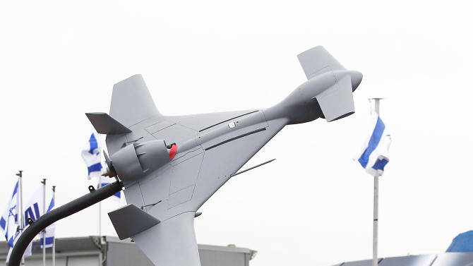 A visitor walks past the Israeli stand, displaying the Harop drone, top, a long endurance loitering weapon system during the first day of the Paris Air Show at Le Bourget airport, north of Paris, Monday June 17, 2013.(AP Photo/Remy de la Mauviniere)
