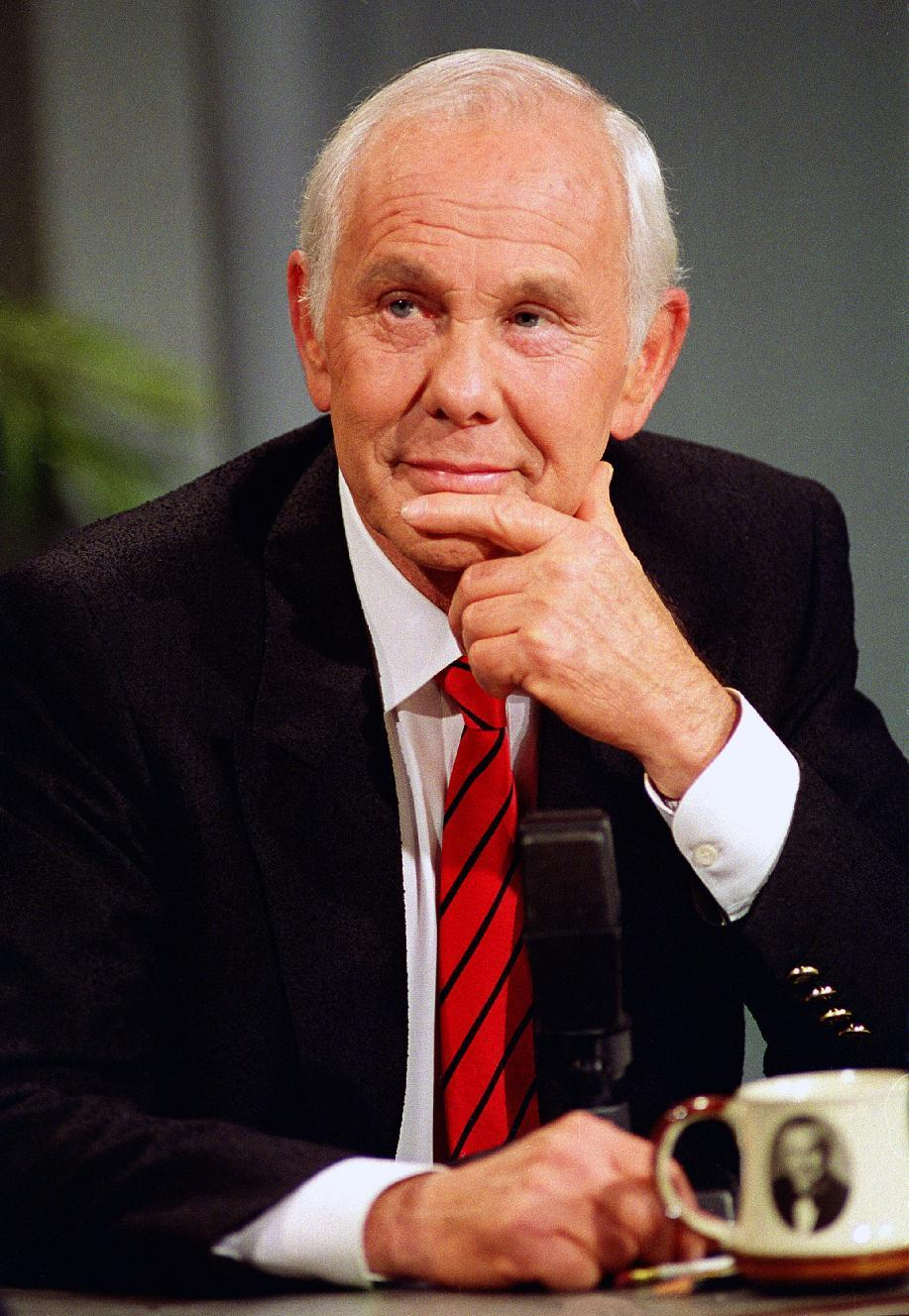"FILE - This May 22, 1992 file photo shows talk show host Johnny Carson, with his personalized coffee cup in front of him, watching clips from earlier shows during the last taping of the ""Tonight Show"" in front of family and friends in Burbank, Calif.  (AP Photo/Douglas C. Pizac, file)"