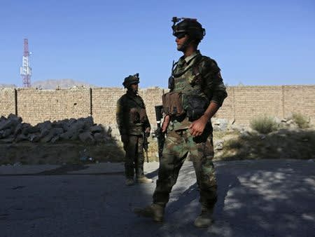 Afghan security forces inspect the site of a suicide bomb attack in Kabul