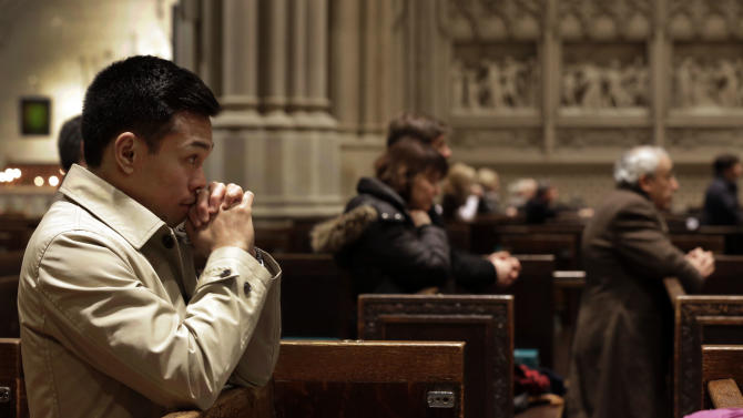 Worshippers attend the 12 noon Mass in New York's St. Patrick's Cathedral,  Monday, Feb. 11, 2013. Worshippers at New York's St. Patrick Cathedral are among those surprised to hear that the Pope plans to resign later this month. (AP Photo/Richard Drew)