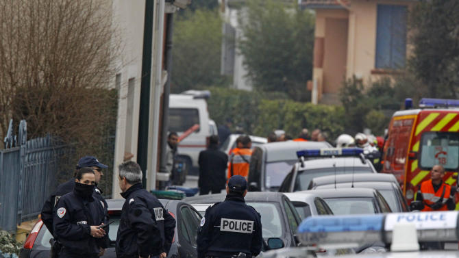 Police officers and firefighters stand next to a building in Toulouse, France, Wednesday, March 21, 2012 where a suspect in the shooting at he Ozar Hatorah Jewish school has been spotted. French police exchanged fire and were negotiating Wednesday with the gunman who claims connections to al-Qaida and is suspected of killing three Jewish schoolchildren, a rabbi and three paratroopers. (AP Photo/Remy de la Mauviniere)