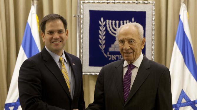 Israel's President Shimon Peres, right, shakes hands for photographers with US Sen. Marco Rubio, R-Fla. during their meeting in the President's residence in Jerusalem, Wednesday, Feb. 20, 2013. Rubio is on a visit to the region. (AP Photo/Sebastian Scheiner)