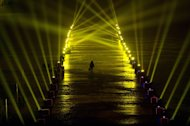 A reveller walks on a frozen lake between spotlights during a countdown event for the new year at the Summer Palace in Beijing on December 31, 2013
