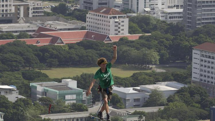 U.S. slackliner Andy Lewis of Calif. balances on a 169 meters (555 feet)-long slackline in Bangkok, Thailand Wednesday, July 23, 2014. Lewis' balancing act was to promote a consumer product. (AP Photo/Sakchai Lalit)