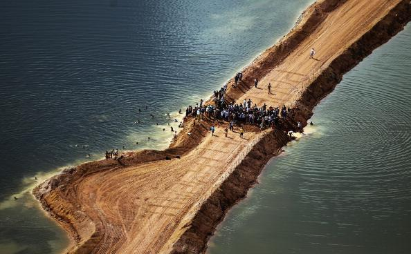 Residents who are being displaced by the Belo Monte dam and supporters stand atop a temporary earthen dam at the construction site after removing a strip of earth to restore the flow of the Xingu River as a protest against the construction on June 15, 2012 near Altamira, Brazil.