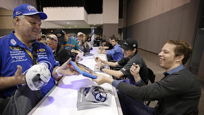 Defending Sprint Cup champions Brad Keselowski hands back an autographed item to a fan during NASCAR Preview 2013, Saturday, Feb. 9, 2013, in Charlotte, N.C. (AP Photo/Bob Leverone)