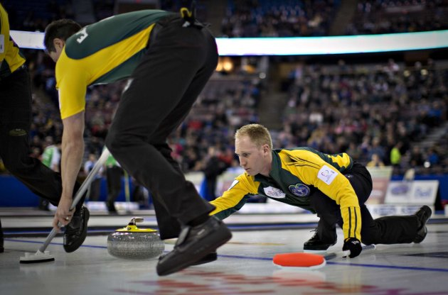 Northern Ontario skip Jacobs watches the line of his shot as teammate Harnden sweeps during play at the Canadian Men's Curling Championships in Edmonton