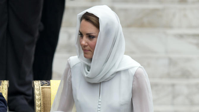 Kate, the Duchess of Cambridge puts her shoes back on following a visit to a mosque in Kuala Lumpur, Malaysia, Friday, Sept. 14, 2012. (AP Photo/Mark Baker)