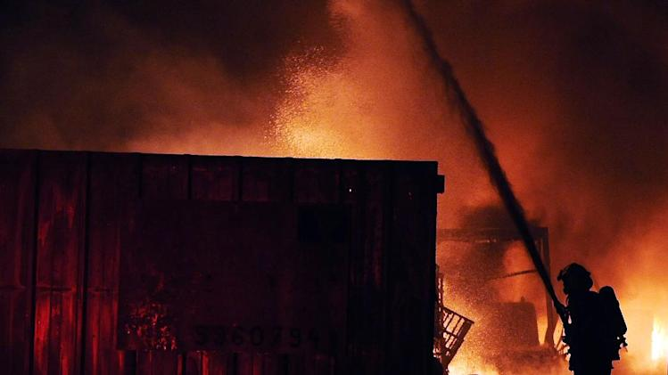 Israeli firefighters extinguish a burning factory hit by a rocket fired from the Gaza Strip on June 28, 2014 at an industrial zone in the southern city of Sderot