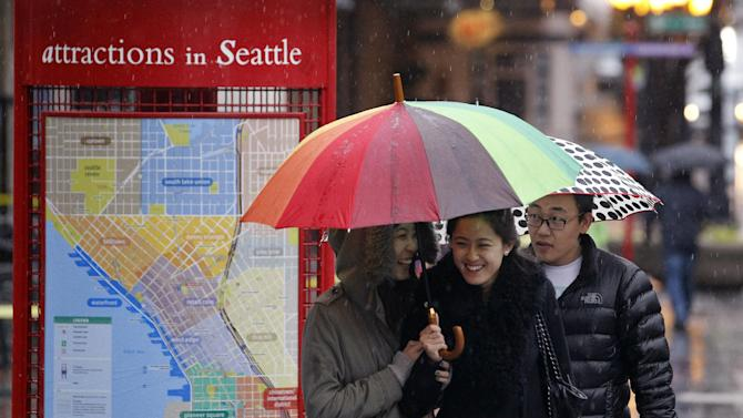 Visitors to downtown Seattle huddle under umbrellas while walking in the shopping district Monday, Nov. 19, 2012, in Seattle. Wet and windy weather with mountain snow will continue this week in Washington, but there may be a lull for turkeys to land on Thanksgiving Day tables, forecasters said. More Pacific storms that started rolling across the Northwest in waves over the weekend are on their way, according to the National Weather Service. (AP Photo/Elaine Thompson)