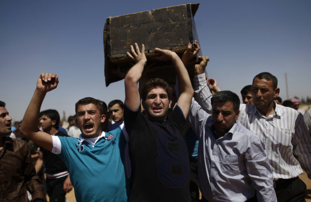 Relatives and mourners carry the coffin of Free Syrian Army fighter Emad Nimeh, 18, who was killed today in an airstrike, during his funeral procession in Al-Bab, on the outskirts of Aleppo, Syria, Friday, Aug. 24, 2012. (AP Photo/Muhammed Muheisen)