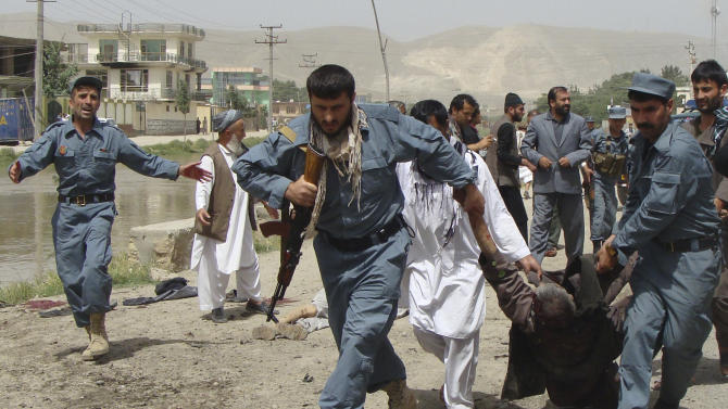 """Afghan policemen evacuate a wounded person after a suicide bomber struck outside a provincial council headquarters in Pul-i-Khumri, Baghlan province, northern Afghanistan, Monday, May 20, 2013, killing the council chief and at least more than a dozen others, authorities said. Afghan President Hamid Karzai condemned the bombing saying the killing of civilians shows the """"true nature"""" of the Taliban, who seek to re-establish the strict interpretation of Islamic law they imposed for five years before being ousted in the 2001 U.S.-led invasion over its sheltering of al-Qaida's terrorist leadership. (AP Photo/Jawed Basharat)"""