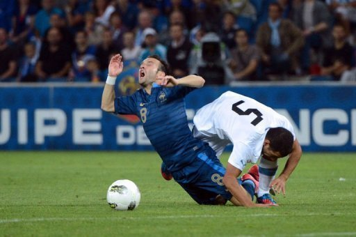French midfielder Mathieu Valbuena (L) collides with Uruguayan midfielder Walter Gargano