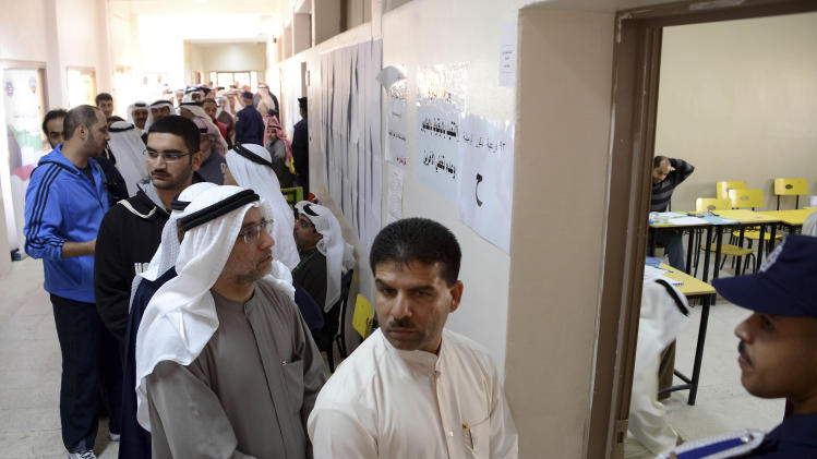 Kuwaiti citizens wait in line to cast their vote at a polling station in Rumaithiya, Kuwait on Saturday, Dec. 1st, 2012. The general election to appoint a new Parliament is the fifth since mid-2006, and the second this year.(AP Photo/Gustavo Ferrari)