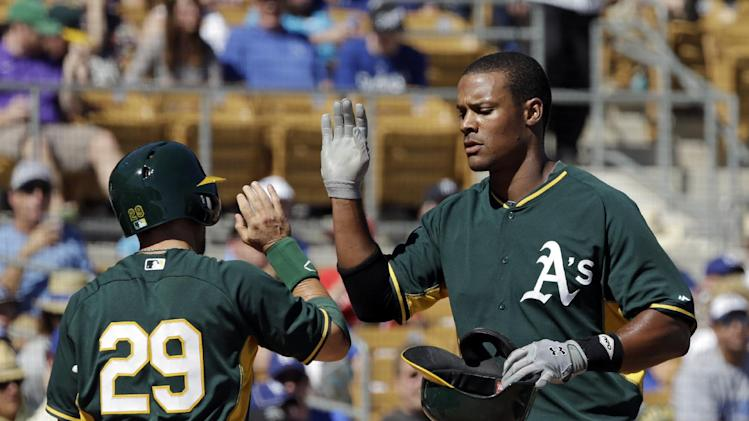 Oakland Athletics' Michael Taylor is greeted by Sam Fuld (29) after Taylor's solo home run off Los Angeles Dodgers starting pitcher Hyun-Jin Ryu in the fifth inning of a spring exhibition baseball game Monday, March 10, 2014, in Glendale, Ariz