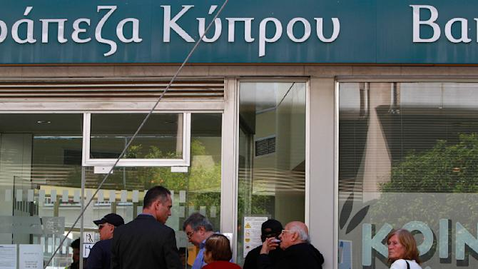 People wait outside a branch of Bank of Cyprus in Nicosia, Cyprus, Thursday, March 28, 2013. Cypriots get their first chance to access their savings in almost two weeks when the country's banks reopen Thursday - albeit with strict restrictions on transactions - after being closed due to the country's acute financial crisis. Lines were starting to form outside banks Thursday morning ahead of the official opening for six hours at noon (1000 GMT). (AP Photo/Petros Karadjias)