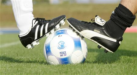Players wearing Puma and an Adidas soccer shoes pose before a friendly soccer match between German sports goods firm Puma and German sporting goods maker Adidas in Herzogenaurach
