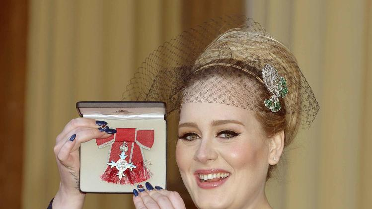 British singer Adele Adkins shows off her MBE for services to music presented to her by the Prince of Wales at Buckingham Palace in London