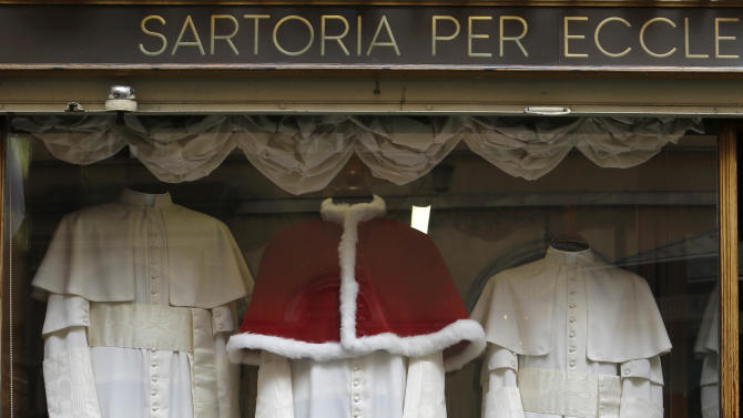 Three sets of papal outfits - small, medium and large sizes - which will be sent to the Vatican for the new pope, are displayed in the window of the tailoring shop Gammarelli, in Rome, Monday, March 4, 2013. For over a half century the Gammarelli family has produced the pope robes in three different sizes that are delivered before the conclave meets, in order to fit the newly elected popes. (AP Photo/Andrew Medichini)