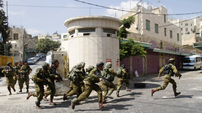 Israeli soldiers run after Palestinian stone throwers, not seen, in the Israeli-controlled area of the West Bank city of Hebron, Monday, Sept. 10, 2012. Palestinian demonstrators fed up with high prices and unpaid salaries shuttered shops, halted traffic with burning tires and closed schools throughout the West Bank on Monday in the largest show of popular discontent with the governing Palestinian Authority in its 18-year history.  (AP Photo/Nasser Shiyoukhi)