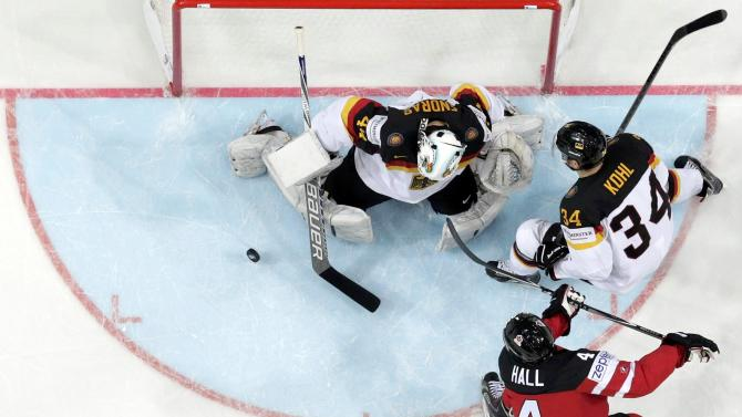 Germany's goaltender Endras and Kohl defend against Canada's Hall during their Ice Hockey World Championship game at the O2 arena in Prague