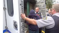 Sub-Lt. Jeffrey Paul Delisle covers his face leaving a Halifax court earlier this moneth where he pleaded guilty to breach of trust and two counts of passing information