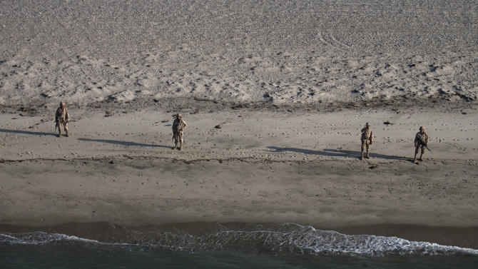 Navy marines search in the beach by foot after a fishing boat capsized near the town of San Felipe, Mexico, Monday,July 4, 2011. A U.S. tourist died after a fishing boat capsized in an unexpected storm in the Gulf of California off the Baja California peninsula and of the 44 people on the boat, seven U.S. tourists remain missing along with one Mexican crew member, the Mexican navy said. (AP Photo/Francisco Vega)