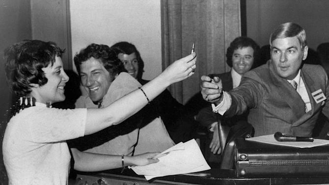"FILE - In this May 18, 1971 file photo, Evelyn Y. Davis, holds up a bullet from an ammunition bandolier she wore to a shareholders meeting of 20th Century-Fox Film Corp. in Wilmington, Del. as company official Charles M. Lewis reaches for it. Davis, commenting on the election of a new board of directors said, ""Here, fight it out."" For decades, Davis, who has been buying a few shares of big companies, attends their annual meetings, turning them into her personal stage. But in 2012, Davis didn't show up at any company's annual meeting. Age has finally made her do what the most powerful CEOs in America couldn't: Give it a rest. ""I'm not so young anymore,"" said Mrs. Davis, 82. (AP Photo)"