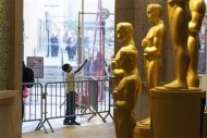 A boy points at the display of Oscars statues on the red carpet during preparations for the 85th Academy Awards in Hollywood, California February 23, 2013. REUTERS/Lucas Jackson