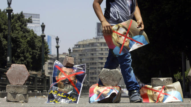 "An Egyptian protester holds posters depicting U.S. Ambassador to Egypt Anne Patterson and President Mohammed Morsi blocking an entrance to Tahrir Square in Cairo, Egypt, Friday, June 28, 2013. Arabic on the poster at left reads,"" the end of the reign of terror."" Elsewhere, thousands of supporters of Egypt's embattled president are rallying in the nation's capital in a show of support ahead of what are expected to be massive opposition-led protests on June 30 to demand Mohammed Morsi's ouster. (AP Photo/ Amr Nabil)"