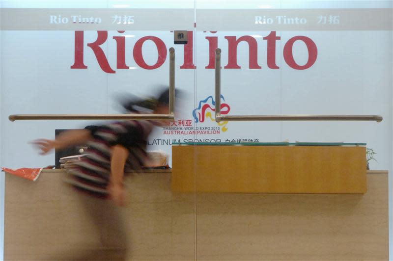 A woman runs past the reception desk of the Rio Tinto Limited Shanghai Representative Office in Shanghai