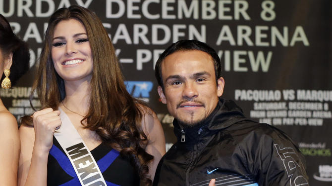 Juan Manuel Marquez, right, poses for photos with Miss Mexico Karina Gonzalez during a news conference, Wednesday, Dec. 5, 2012, in Las Vegas. Marquez is scheduled to face off against Manny Pacquiao in a welterweight fight boxing match on Saturday. Gonzalez is competing in next week's Miss Universe pageant in Las Vegas. (AP Photo/Julie Jacobson)