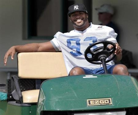 Injured Indianapolis Colts defensive end Dwight Freeney smiles as he drives a golf cart before practice at the Miami Dolphins training facility in Davie, Florida