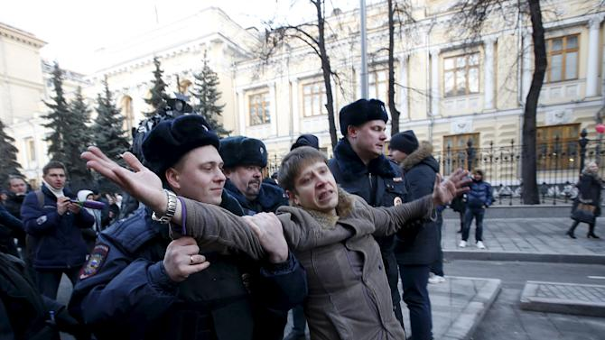 Police officers detain activist who was taking part in rally of foreign currency mortgage holders near Central Bank headquarters in central Moscow