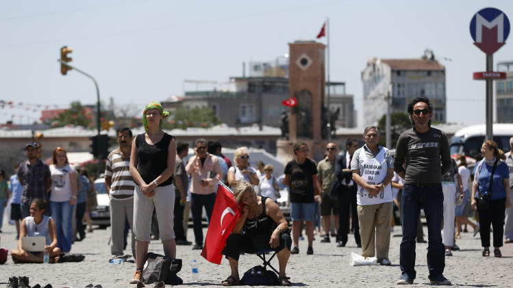 A woman holding a Turkish national flag, sits and rests as people gather for a silent protest at Taksim Square in, Istanbul, Turkey, Thursday, June 20, 2013. After weeks of sometimes violent confrontation with police, Turkish protesters have found a new form of resistance: standing still and silent. (AP Photo/Petr David Josek)