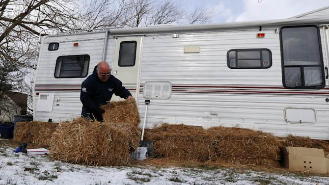 Anthony Cavallo uses hay to insulate his trailer in preparation for a cold night, Wednesday, Jan. 23, 2013, in Union Beach, N.J. Cavallo had to buy the trailer out of pocket and place it next to his home damaged by Superstorm Sandy because he is yet to receive storm aid. Cold weather is bringing extra worries to residents of the areas hit by Sandy. The deep freeze will continue into Thursday and Friday. There's a chance of snow Friday afternoon and evening, but accumulations are expected to be minor. (AP Photo/Julio Cortez)