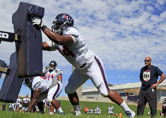 CORRECTS PLAYER TO DEFENSIVE END JULIUS WARMSLEY, NOT TACKLE MATT FEILER AS ORIGINALLY SENT - Houston Texans defensive end Julius Warmsley hits the sled during a joint practice between the Denver Broncos and the Texans on Wednesday, Aug. 20, 2014, in Englewood, Colo