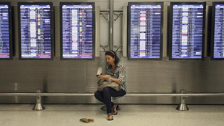 FILE - In this Nov. 22, 2011, file photo, Victoria Puerto checks her flight information and tickets near flight status boards at the Miami International Airport in Miami. Airlines are slowly, steadily recovering from their meltdown five years ago, when, under the strain of near-record consumer travel demand, their performance tanked. Industry performance for all four measurements was slightly better in 2011 compared with 2010, according to the report being released Monday, April 2, 2012. (AP Photo/J Pat Carter, File)