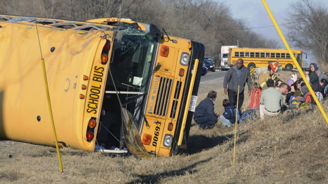 Rescue personnel attend to children from Newport Elementary School after their school bus overturned Friday, April 5, 2015, near Wadsworth, Ill. There were about two dozen children on board. There was no immediate word on injuries. (AP Photo/Lake County News-Sun, Thomas Delany Jr.) CHICAGO LOCALS OUT
