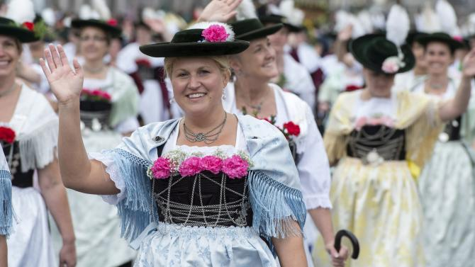 A woman dressed in traditional Bavarian clothes waves during the Oktoberfest parade in Munich