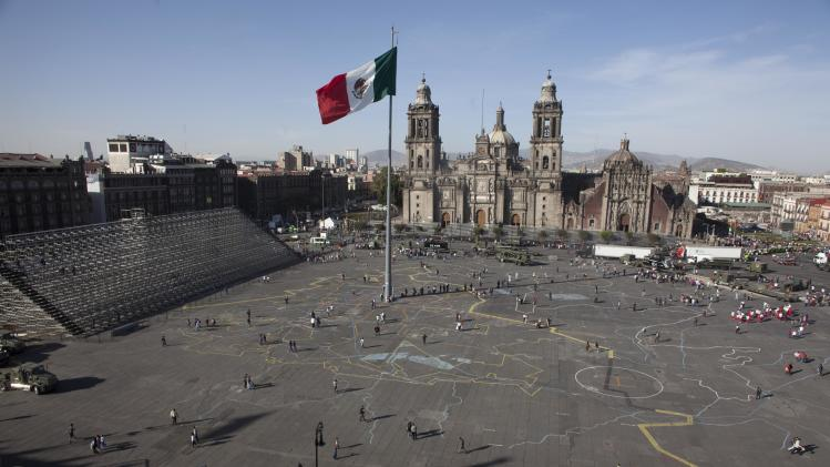 Pedestrians make their way across the Zocalo plaza in downtown Mexico City, Tuesday, Nov. 20, 2012. The Zocalo was the center of the Aztec island empire that became Mexico City after the Spanish conquest, and it remains the heart of the capital. The massive open plaza is bounded by Mexico City's main cathedral, along with the National Palace that houses the federal government and the ruins of the Templo Mayor, which was the central temple of the ancient Aztecs. Entrance to the cathedral and part of the National Palace are free, and the Zocalo itself is often filled with open-air entertainment, with street vendors, painted Aztec dancers, traditional healers and the occasional political demonstration all competing for attention. (AP Photo/Alexandre Meneghini)