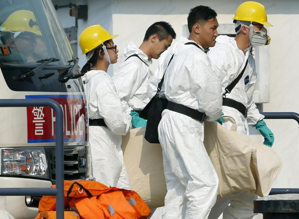 Workers carry a dead body after it was recovered during search and rescue operations after a boat packed with revelers on a long holiday weekend collided with a ferry and sank off Hong Kong, killing at least 36 people and injuring dozens, Tuesday, Oct. 2, 2012.   (AP Photo/Vincent Yu)