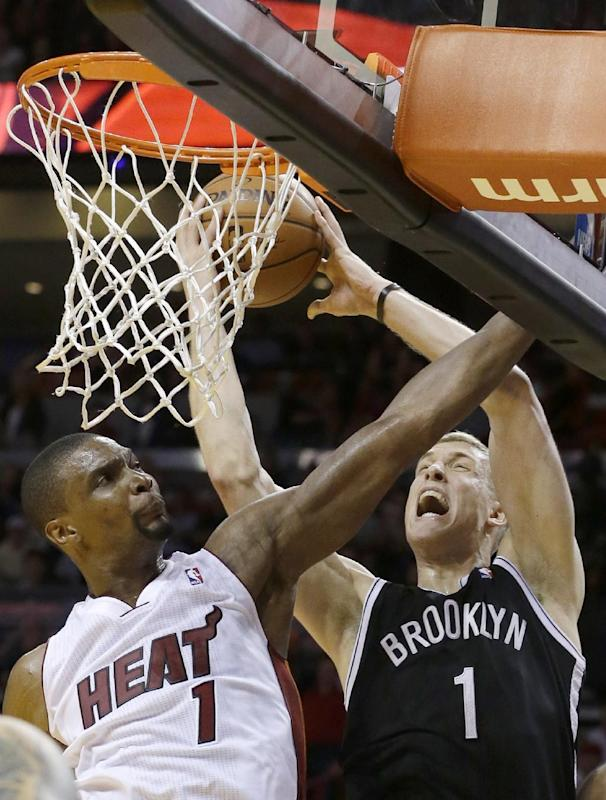 Brooklyn Nets forward Mason Plumlee, right, goes up for a shot against Miami Heat center Chris Bosh during the second half of an NBA basketball game, Tuesday, April 8, 2014 in Miami. The Nets defeated the Heat 88-87. (AP Photo/Wilfredo Lee)