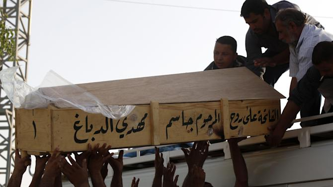 Family members of Bilal Aziz, 20, who was killed in a car bomb attack load his coffin onto a vehicle before burial in Najaf, 100 miles (160 kilometers) south of Baghdad, Iraq, Wednesday, June 13, 2012. A wave of bombings targeted religious processions during the annual pilgrimage commemorating the 8th century death of a revered Shiite imam, killing and wounding scores of people, police said. (AP Photo/Alaa al-Marjani)