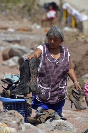 A woman cleans shoes after her home was affected by…