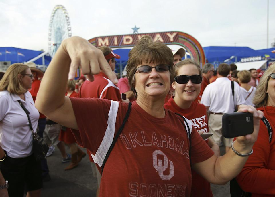 An Oklahoma  fan gives an upside down horns sign as the Texas team arrives for their  NCAA college football game at the Cotton Bowl Saturday, Oct. 13, 2012, in Dallas. (AP Photo/Michael Mulvey)